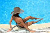 Kobieta siedzi na półce w basenie. — Zdjęcie stockowe