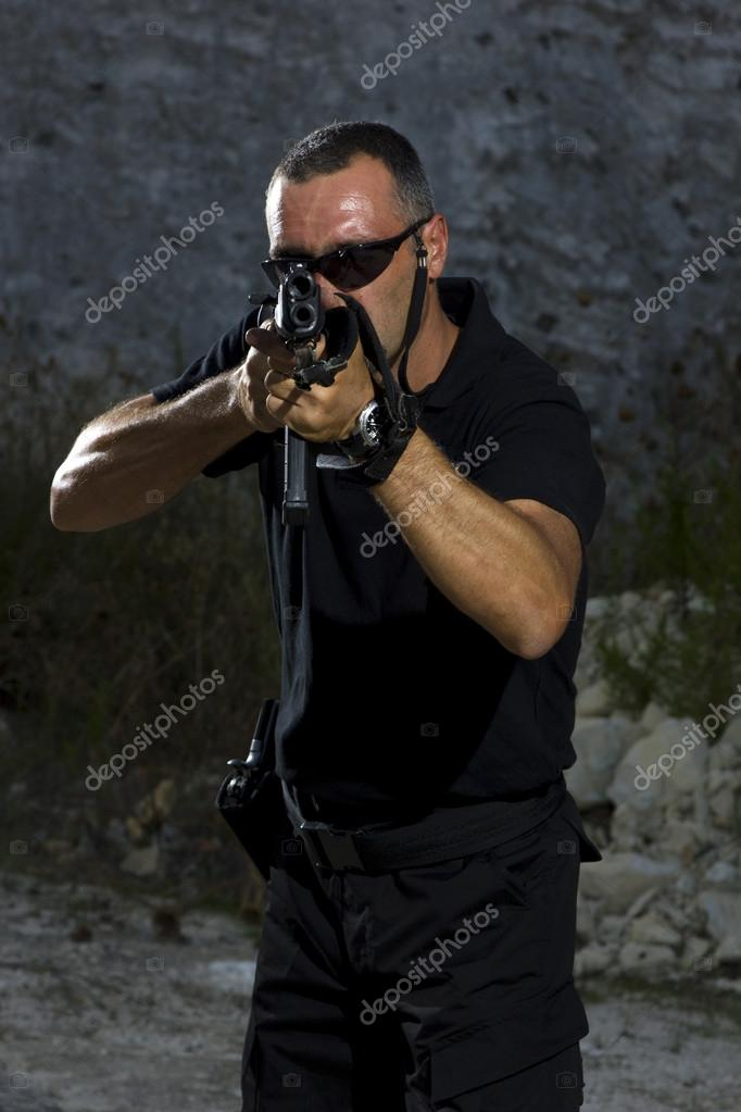 Man shooting on an outdoor shooting range, selective focus — Stock Photo #14722487
