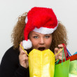 Beautiful young woman wearing a Santa hat and holding shopping b — Stock Photo