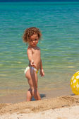 Little girl playing with a ball on the beach — Stock Photo