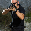 Man shooting on an outdoor shooting range - Stock Photo