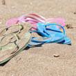 Beach sandals or tongs on a sandy beach — Stock Photo
