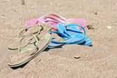 Beach sandals or tongs on a sandy beach — Stock Photo