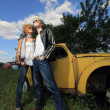 A young couple on a old car in a field — Stock Photo