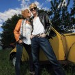 A young couple on a old car in a field - Stock Photo
