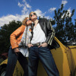 A young couple on a old car in a field - Foto de Stock