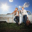 A young couple on a old car in a field - Foto Stock
