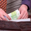 Man is paying with euro banknotes - Stock Photo