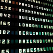 Flights information board in airport - Stock Photo
