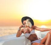 Young sexy woman in white bikini enjoying the sunset — Stock Photo
