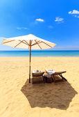 Bedden en een paraplu op een strand — Stockfoto