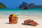 Coconut cocktail and sandals on the beach — Stock Photo