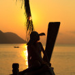 Woman in sarong on a long tailed boat at sunrise — Stock Photo #22667609