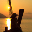 Woman in sarong on a long tailed boat at sunrise — Stock Photo #22667627