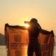 Woman in sarong on the beach at sunrise — Stock Photo