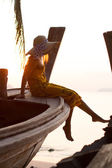 Woman in sarong on a long tailed boat at sunrise — Stock Photo