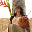 Woman in sarong on a coconut tree at the beach - Stock Photo
