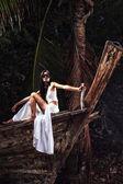 Mujer en bote de madera con un cuchillo — Foto de Stock