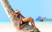 Woman sitting on a coconut tree on Phi Phi — Stock Photo