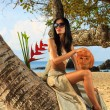 Stock Photo: Woman on a coconut tree at the beach in Thailand