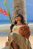 Woman in sarong on a coconut tree — Stock Photo