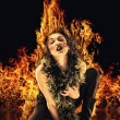 Vampire woman surrounded by fire - Stock Photo