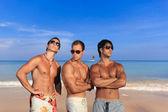 Drie knappe mannen op het strand — Stockfoto