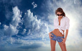 Woman in jeans shorts standing on blue cloudy sky — Stock Photo