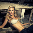 Blond woman posing in front of an old wooden ship wreck — Stock Photo