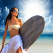 Surfer girl with surfboard at a beach - Stok fotoğraf
