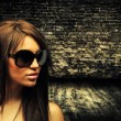 Brunette woman on brick wall - Stock Photo