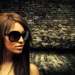 Brunette woman on brick wall — Stock Photo