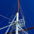 Boat masts against a blue sky - Stock Photo