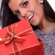 Beautiful young smiling woman with a gift — Stock Photo