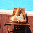 Young woman lies near the swimming pool — Stock Photo