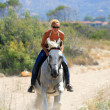 Beautiful blonde woman in bikini riding a white horse — Stock Photo #25542811