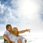 Mature couple sitting on the beach — Stock Photo