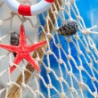 Fishing net with buoy and shell - Stock Photo