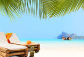 Strohhut auf liegestuhl am strand — Stockfoto