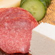 Feta and ementhal cheese with salami and cucumber — Stock Photo