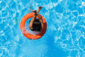 Jumping in the buoy at the swimming pool — Stock Photo