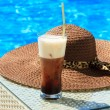 Stock Photo: Ice coffee Fredo against blue clear water of swimming pool