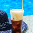 Ice coffee Fredo against blue clear water of the swimming pool — Stock Photo