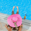 Womsitting on ledge of pool. — Stock Photo #27087461