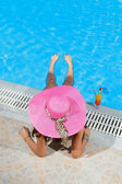 Woman sitting on the ledge of the pool. — Stock Photo