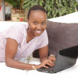 Happy African American young woman using a laptop — Stock Photo