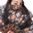 Spanish  woman behind traditional fan. — Stock Photo