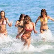Happy teenagers playing in the sea — Stockfoto