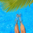 Women legs splashing in tropical swimming pool — Stock Photo