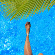 Women legs splashing in tropical swimming pool — Foto de Stock